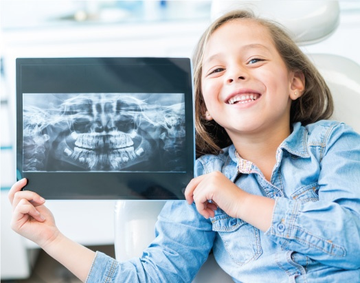 young, smiling girl holding up an x-ray of her teeth