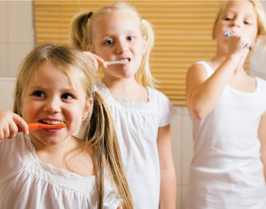 three young sisters brushing their teeth together