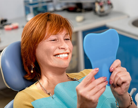woman in dental chair smiling at herself in mirror